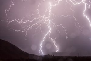 image shows lightning at night behind a landscape of mountains and valleys